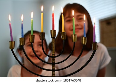 Two happy Jewish sisters looking and singing at a beautiful menorah candelabra glowing on the eight day of Hanukkah Jewish holiday.