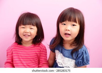 Two Happy kid girl smile to you isolated on pink background, asian