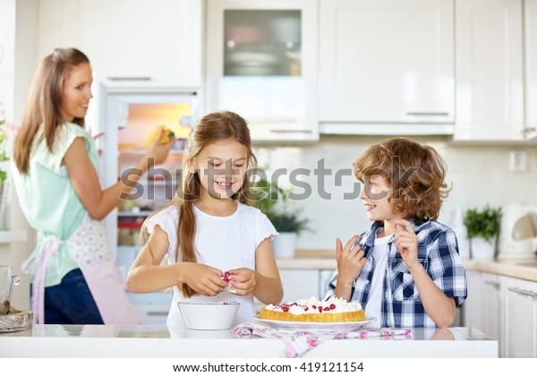 Two happy kids baking a fruit cake with red currants in the kitchen