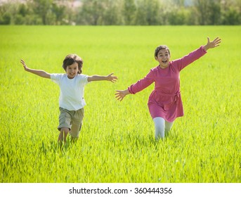 Two happy kids in green wheat