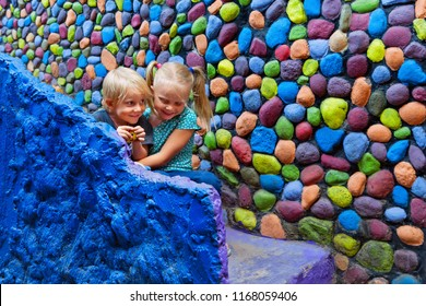Two happy kids have fun together sitting outside home on colorful stone steps. Playful girl hug laughing younger brother. Travel lifestyle, walking city tour on summer family vacation with children.