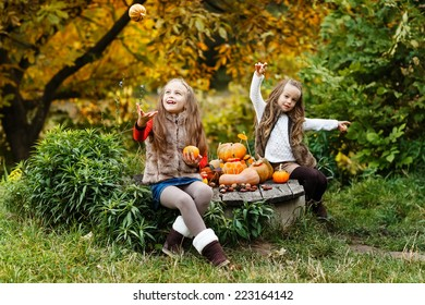 Two happy kids having fun with pumpkins the park. Autumn concept