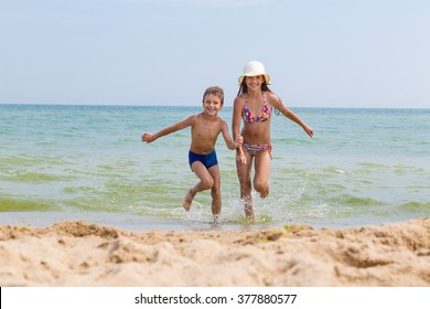 Two happy kids on the beach run out from the sea