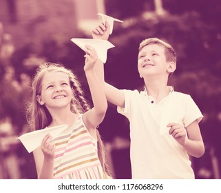two happy kids playing with simple paper planes on sunny day in town
