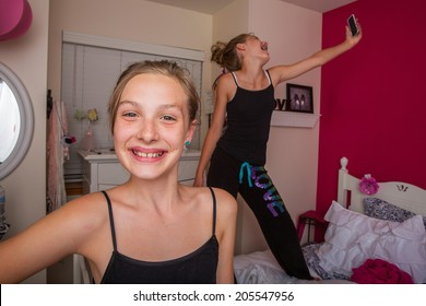 Two happy kids playing in their room and taking selfies with their cellphone