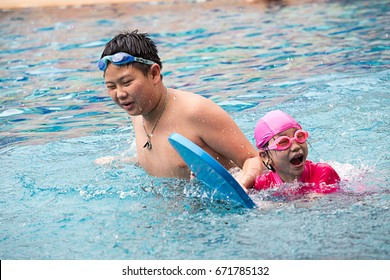 Two happy kids in a swimming pool