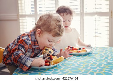 Two happy kids twins boy girl eating breakfast waffles with fruits sitting at table in sunny kitchen early morning with sunlight from behind