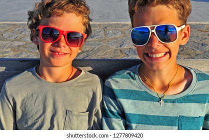 Two happy kids wearing sunglasses outdoors