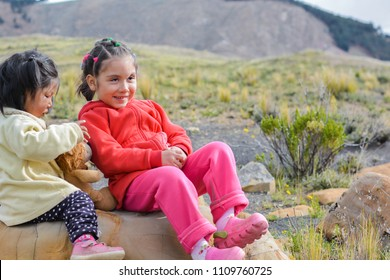 Two happy latin kids sitting on the stone and having a good time.