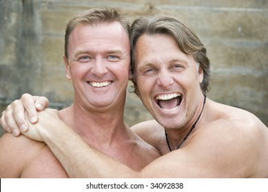Two happy laughing gay men cuddle up together.