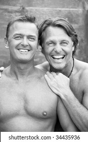 Two happy laughing gay men enjoy a cuddle outdoors.
