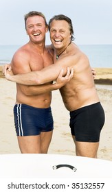 Two happy laughing gay men are hugging on the beach.