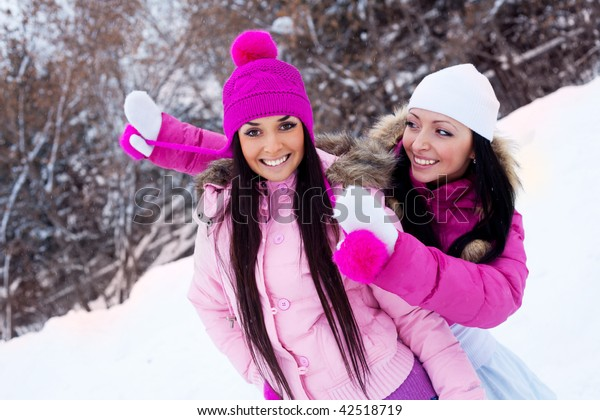 two happy laughing girls having a walk in the winter park