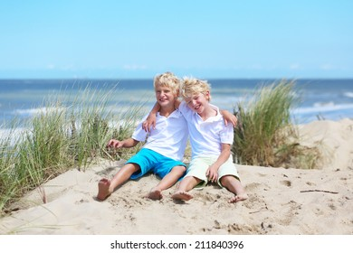 Two happy laughing kids, twin teenager brothers, having fun on the beach playing in sandy dunes, North Sea, Belgian coast