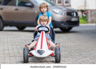 Two happy little boy friends having fun with toy race car in summer garden, outdoors. Active kid pushing the car with younger boy. Outdoor games for children in summer concept.