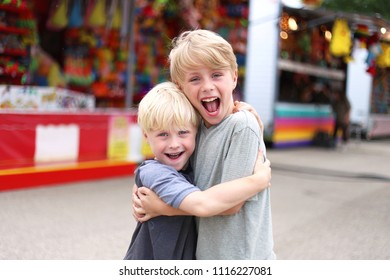 Two happy little boys are smiling and hugging by the midway games at a small town American Carnival