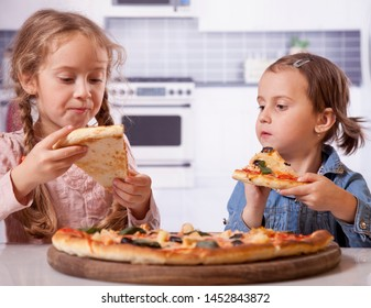 Two happy little child girl friends with pizza slices.