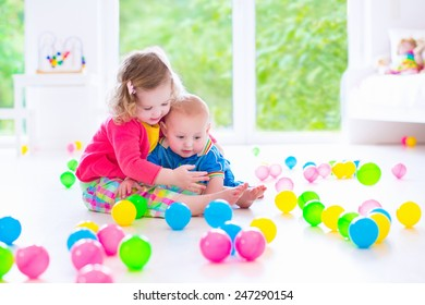 Two happy little children, cute curly toddler girl and a funny baby boy playing together with colorful balls in a white sunny room with big window
