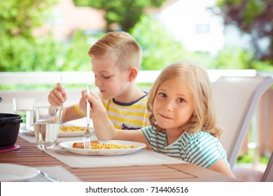 Two happy little children eating healthy breakfast on terrace at home