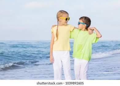 Two happy little children playing on the beach at the day time.  Kids having fun outdoors. Concept of summer vacation and friendly family.