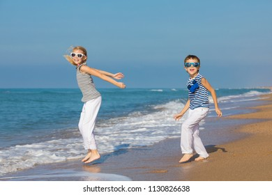 Two happy little children playing on the beach at the day time. They are dressed in sailor's vests. Kids having fun outdoors. Concept of sailors on vacation and friendly family.