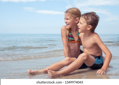 Two happy little children playing on the beach at the day time.  Kids having fun outdoors. Concept of kids on vacation and friendly family.