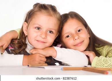 two happy little girls drawing at table