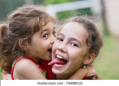 Two Happy little girls embracing and laughing at summer day