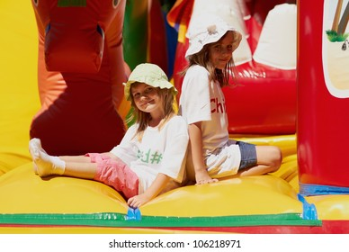 Two happy little girls kids playing in inflatable bouncing castle playground.Pretty small children in panama sun hats.Bright sunny summer day,smiling friendly girls sisters play on inflatable slide