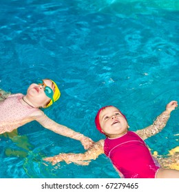 Two happy little girls learning to swim in a pool
