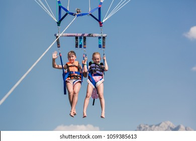 Two happy little girls on parasailing ride, extreme sport