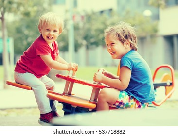 Two happy little girls on teetering board outdoor