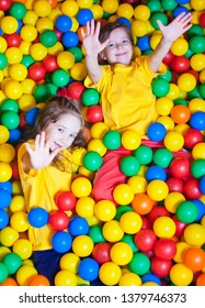 Two Happy little girls playing and having fun at kindergarten with colorful balls in play center