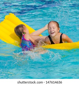 two happy little girls playing  in the pool on the airbed