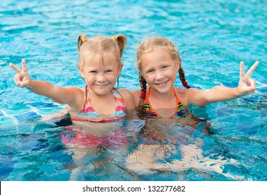 two happy little girls  in the pool
