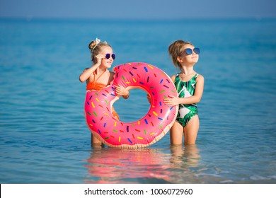 Two happy little girls rest on the sea. Smiling girl swimming in a circle in the sea