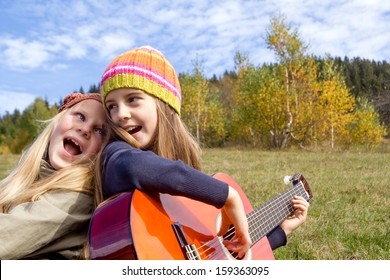 Two happy little girls singing and playing a guitar