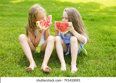 Two Happy little girls sit on a grass eating watermelon in summertime. Two Happy little girls Having Fun outdoors in summer.