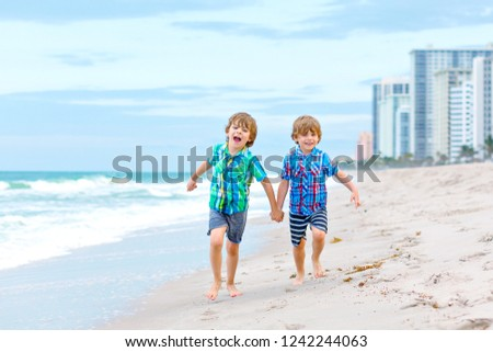 2324fb17c Two happy little kids boys running on the beach of ocean. Funny cute  children,