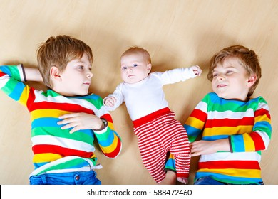 Two happy little preschool kids boys with newborn baby girl, cute sister. Siblings, twins children and baby playing together. Kids bonding. Family of three, love. kids in colorful fashion clothes