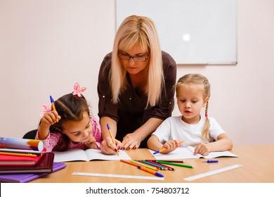 two happy little schoolgirls study in class, the teacher explains