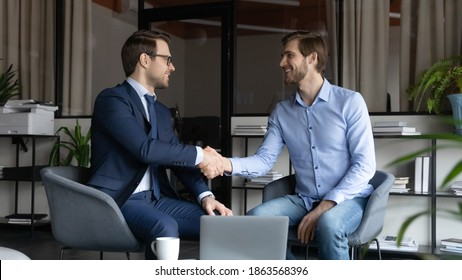 Two happy male business partners handshaking reaching agreement on negotiations, smiling leader greeting skilled capable worker employee with reward promotion, content client and banker finishing deal