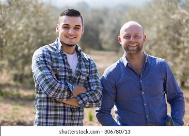 Two happy male farmers standing with spades at plantation