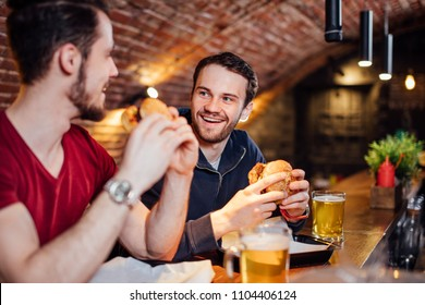 Two happy male friends having dinner at popular burger bar. Young people sitting, talking and eating burgers, drinking beer.