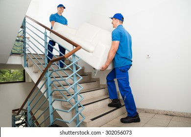 Two Happy Male Movers In Uniform Carrying White Sofa On Staircase