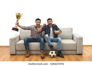 The two happy men with a cup watch a football on the sofa
