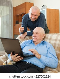 two happy men with laptop at home