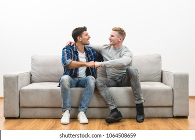 The two happy men on the sofa gesture on the white wall background