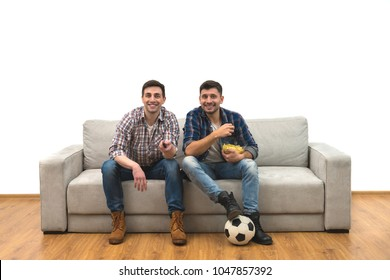 The two happy men watch a football on the sofa on the white background