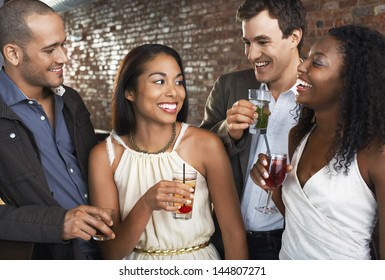 Two happy multiethnic couples with drinks at the bar